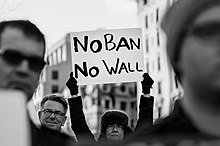 "Image from the protests at Washington D.C where the protester is holding a banner that says ""No ban no wall"" which became a popular hashtag on the internet and social media."
