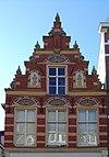 foto van Pand met versierde trapgevel met reliëfs van Johannes de Doper en Johannes de Evangelist