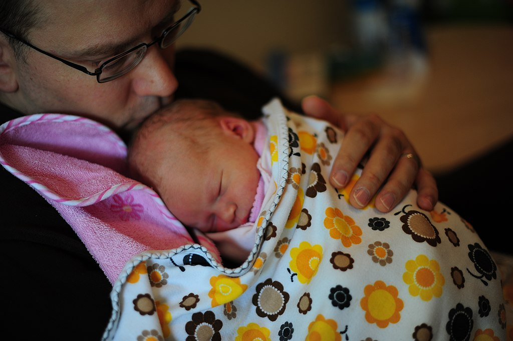 Father holding daughter in swaddling clothes