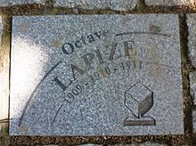Photographie d'un pavé gris portant l'inscription « Octave Lapize 1909-1910-1911 ».