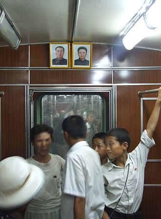 Pyongyang Metro - North Koreans riding the Pyongyang Metro in 2012. The portraits above the door are of former leaders Kim Il-sung and Kim Jong-il.
