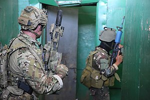 Colour photo of two soldiers armed with rifles inside a building