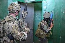 Farbfoto von zwei Soldaten, die mit Gewehren innerhalb eines Gebaudes bewaffnet sind