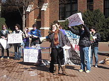 "A college-aged female in jacket and scarf holds the microphone attachment of a bullhorn while other students hold protest signs behind her. Two with large red X's over the words read ""Free Speech"" and ""Access."""