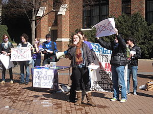 """A college-aged female in jacket and scarf holds the microphone attachment of a bullhorn while other students hold protest signs behind her. Two with large red X's over the words read """"Free Speech"""" and """"Access."""""""