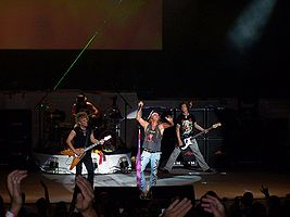Poison live at Holmdel, New Jersey in 2006. Left to right: C.C. DeVille, Rikki Rockett, Bret Michaels and Bobby Dall.