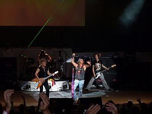 Poison (American band) - Poison live at Holmdel, New Jersey in 2006. Left to right: C.C. DeVille, Rikki Rockett, Bret Michaels and Bobby Dall.