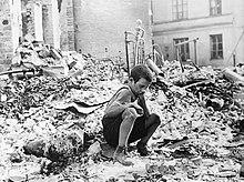 Photo noir et blanc prise en septembre 1939, à Varsovie. Au centre de la photo, un enfant se tient accroupi dans les gravats d'un bâtiment en ruine.