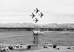 Four single-engined swept-wing jets in a diamond formation above an air base
