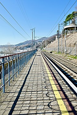 Railway along the sea coast with a tunnel in the mountain on the horizon.jpg