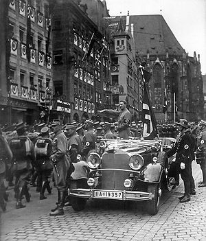 Blutfahne - Adolf Hitler reviewing SA members in 1935. He is accompanied by the Blutfahne and its bearer SS-Sturmbannführer Jakob Grimminger.