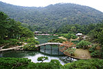 A pond with a bridge and islands in a park setting surrounded by wood and in front of a hill.