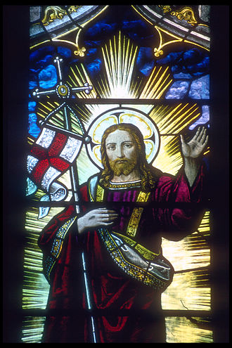 Anglicanism - Jesus Christ supporting an English flag and staff in the crook of his right arm depicted in a stained glass window in Rochester Cathedral, Kent