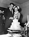 Ronald Reagan and Nancy Reagan cutting cake at William Holden's house after their wedding in Toluca Lake, California.jpg
