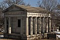 Light colored stone mausoleum flanked by four columns. Door is aged metal.
