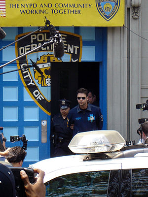 "Two police officers escorting a man wearing sunglasses and a blue shirt out of a door in a wall on a city street. The wall and door are painted with the logo of the New York City Police Department. Above it is a promotional banner with the words ""The NYPD and community working together"". In the foreground is a police car. People taking photographs and microphones on booms intrude on the edges of the image."