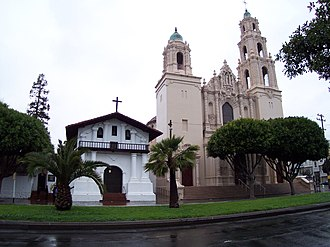 Mexican secularization act of 1833 -  The original Mission San Francisco de Asís adobe structure is the smaller building at left, while the larger structure is a basilica completed in 1918 (the architectural style was influenced by designs exhibited at San Diego's Panama-California Exposition in 1915).