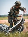 Sgt. Bajrang Lal Shekhawat prepares to pack his parachute after landing on St. Mere Eglise Drop Zone.jpg