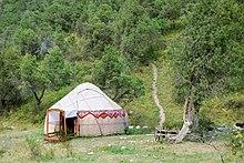 Petite yourte blanche avec des décorations rouge et une porte soutenue par du bois, le long d'une colline boisée où passe un petit chemin