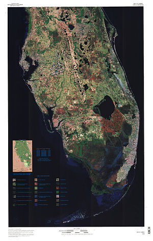 A color satellite image of the lower two thirds of the Florida peninsula: large bodies of water are black, most of the peninsula is spotted green and brown indicating developed and wooded areas; a large chunk of land south of Lake Okeechobee is red, indicating the Everglades Agricultural Area; south of that is a solid swath of dark blue indicating where the Everglades flow in a southwesterly direction into the Gulf of Mexico