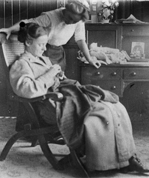 StateLibQld 1 92432 Interior view of a woman mending clothes, ca. 1910