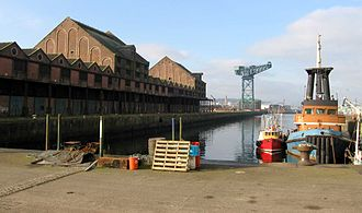 2002 World Monuments Watch - The Sugar Warehouse dominating Scotland's James Watt Dock is a rare, early example of structural cast iron externally expressed. It has lain empty since the last of the local's sugar refinery closed down in 1997.