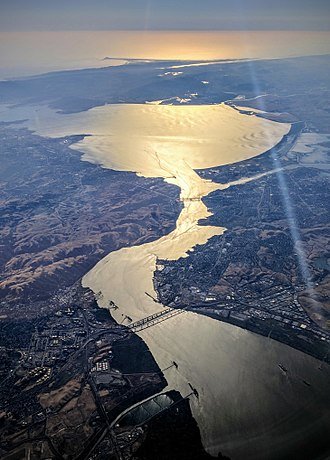 Carquinez Strait - Suisun Bay (bottom), Carquinez Strait (with bridges crossing it), and San Pablo Bay (upper center), with Point Reyes in the background; 2017 evening aerial shot looking west into the sun