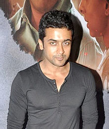 Suriya in a dark, long-sleeved shirt posing for the camera
