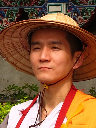Buddhism in Taiwan - Taiwanese Buddhist monk with traditional robes and a bamboo hat.