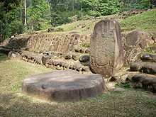 A squat standing stone with a flat front face set against a low stone-faced mound structure at right. The face of standing stone is inscribed but the details are not visible. In front of the stone, at left, lies a flat circular stone, set upon a flat grassy area. Dense vegetation is visible in the background.