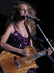 A photograph of Taylor Swift performing at the Cavendish Beach Music Festival in Prince Edward Island, Canada