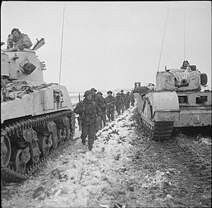 156th (Scottish Rifles) Brigade - Men of the 4th/5th Battalion, Royal Scots Fusiliers pass between a Sherman and a Churchill tank during the 52nd Division's attack towards Stein from Tuddern, 18 January 1945.