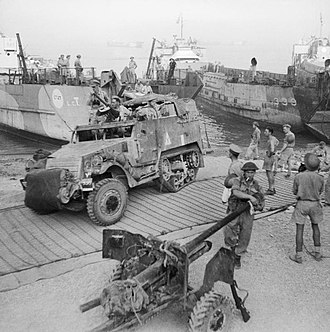Operation Baytown - A half-track and 6-pounder anti-tank gun coming ashore from landing craft at Reggio, Italy, 3 September 1943.