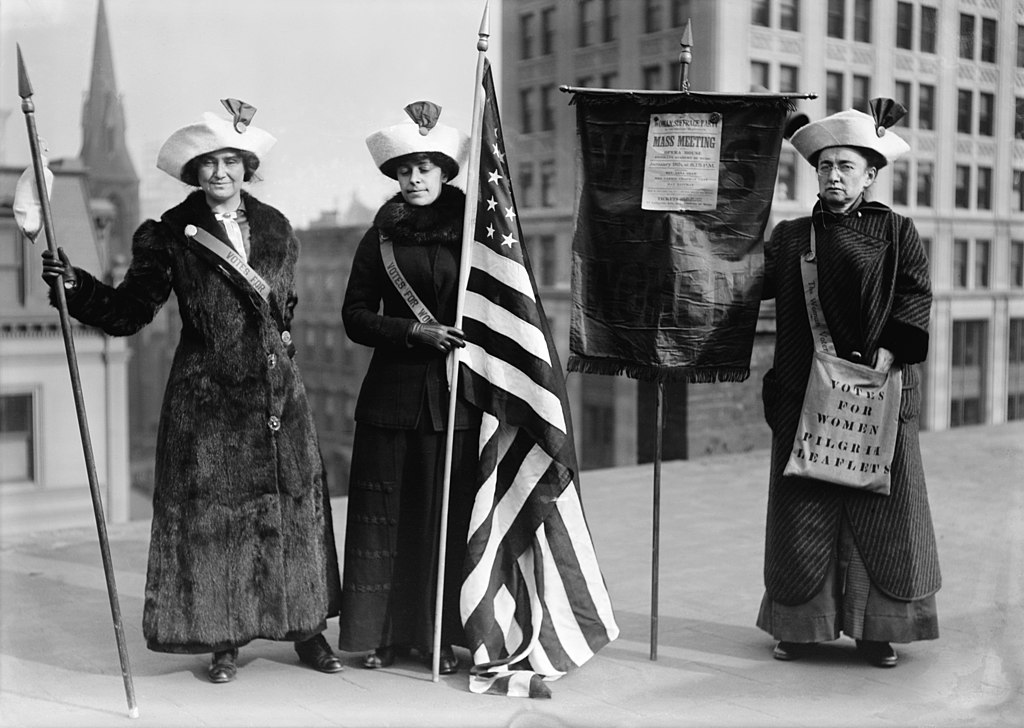 "Suffragettes with flag. Title from unverified data provided by the Bain News Service on the negatives or caption cards. Photo shows women suffrage hikers General Rosalie Jones, Jessie Stubbs, and Colonel Ida Craft, who is wearing a bag labeled ""Votes for Women pilgrim leaflets"" and carrying a banner with a notice for a ""Woman Suffrage Party. Mass meeting. Opera House. Brooklyn Academy of Music. January 9th at 8:15 p.m."""