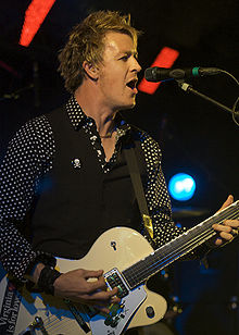 Cheney is singing at a microphone while playing his guitar. He is shown in right profile, he wears a dark shirt with white polka dots, covered by a sleeveless vest. Some stage lights are visible behind him.