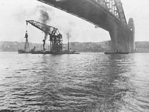The floating crane Titan, being towed under the Sydney Harbour Bridge with the foremast of HMAS Sydney in 1929. The mast is to be installed at Bradleys Head, New South Wales.