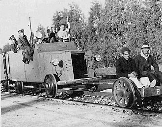 Hostage - A British armoured railway wagon behind a railcar on which two Arab hostages are seated, 1936.