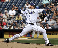 "A man in a white baseball uniform and navy blue cap stands on a dirt mound throwing a pitch with his right hand. He is wearing a black belt, black shoes, and a black baseball glove, and his uniform reads ""Padres"" in navy blue script across the chest, outlined in tan. His cap has two interlocked letters: ""S"" and ""D""."