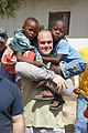 U.S. Navy Boatswain's Mate 2nd Class Nathan Johnson, center, with high speed vessel Swift (HSV-2), carries two children during a community service project at Kinondoni Muslim High School in Dar es Salaam 120629-N-JL721-167.jpg