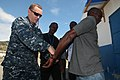 U.S. Navy Lt. Dylan Harmon, the officer in charge for the Naval Criminal Investigative Service, embarked aboard High Speed Vessel (HSV 2) Swift, demonstrates handcuffing procedures with the Authority Port 120221-A-IP644-099.jpg