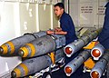 US Navy 030321-N-0923G-002 An Aviation Ordnanceman assists in the unloading of 2000 pound Joint Direct Attack Munition (JDAM) laser-guided GBU-32 Bombs and AIM-120 air-to-air missiles during an ordnance transfer aboard USS Harr.jpg
