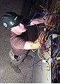 US Navy 040324-N-1261P-009 Construction Electrician 3rd Class Justin Moore assigned to Naval Mobile Construction Battalion Seventy Four (NMCB-74) cross-checks electrical wiring.jpg
