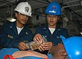 US Navy 050714-N-6236O-012 Cmdr. Marilyn Braddock and Hospital Corpsman 2nd Class Rosalyn Malixi perform first aid on a simulated casualty's sucking chest wound during a mass casualty drill.jpg