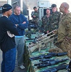 Des militaires autour d'une table sur laquelle est posée plusieurs armes.