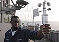 US Navy 061210-N-8547M-001 Aerographer's Mate 3rd Class Akin Akinjoila uses an anemometer to check wind conditions aboard amphibious assault ship USS Saipan (LHA 2).jpg