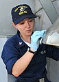 US Navy 100708-N-2013O-014 Information Systems Technician 3rd Class Kathleen Neylon, from Fellsmere, Fla., shines the ship's bell during ship preservation efforts.jpg