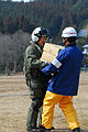 US Navy 110313-N-SB672-014 Lt. Cmdr. Albin Quinko hands over supplies to a Japanese aid worker during earthquake and tsunami relief efforts near S.jpg
