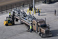 US Navy 111101-N-TZ605-129 Civilian contractors offload lighting equipment on the pier as construction begins on the basketball court for the Quick.jpg