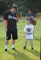 US Navy 111213-N-YU572-103 Miami Marlins catcher Brett Hayes shows the son of Naval Aircrewman 1st Class Scott Barrow how to hold a baseball mitt.jpg
