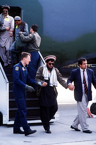 U.S. military personnel (with civilian far right, in suit) at Rhein Main Air Base, Frankfurt, Germany. A civilian volunteer with an Afghan NGO in Germany assists a blinded Afghan Mujahid off the air stair. US military personnel with Mujahideen in 1989.JPEG